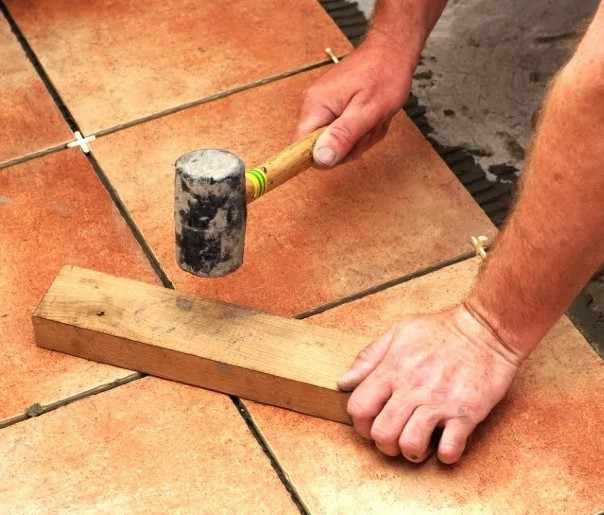 Выравнивание плитки с помощью резинового молотка