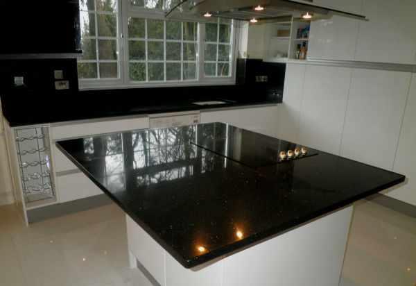 Черная столешница на белой кухне.