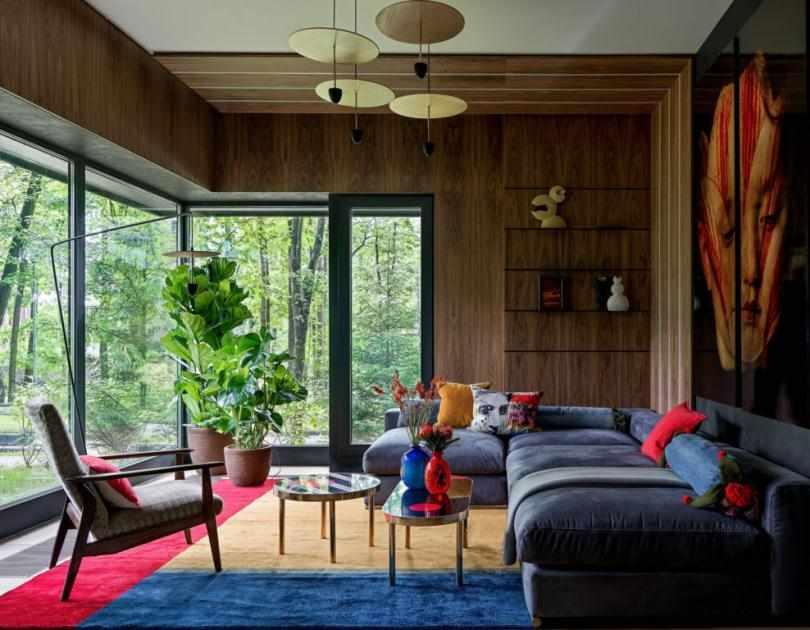 Цветной ковер и серый диван