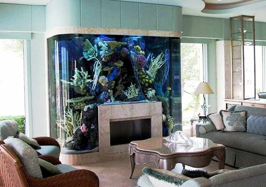 Диваны и столик напротив аквариума с камином