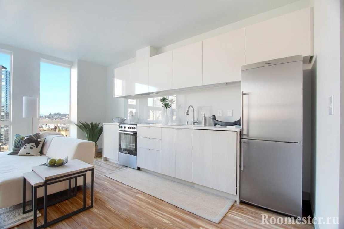 Белая кухня в интерьере с панорамными окнами