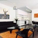 Черная мебель и оранжевый ковер в гостиной
