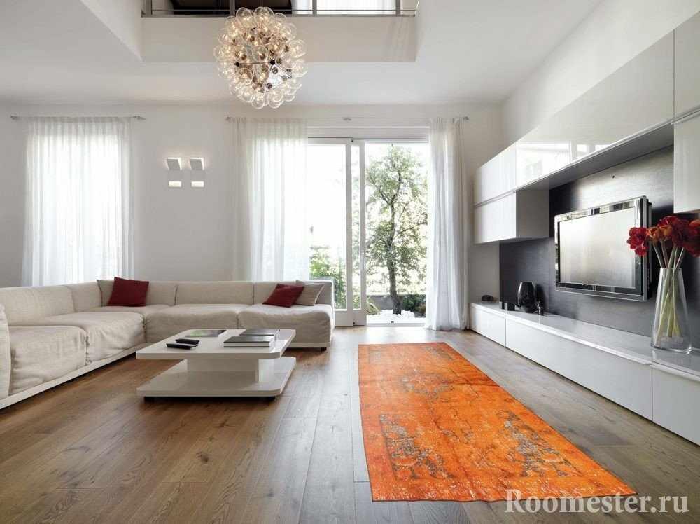 Оранжевый ковер в сочетании с белой мебелью и стенами