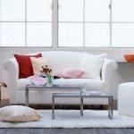 Красные и розовые подушки на белом диване