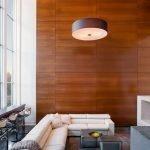 Угловой диван и столик напротив декоративного камина
