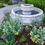 Круглый фонтан среди цветов