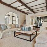 Светлый декор гостиной с деревянным потолком