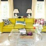 Прозрачный столик и желтый диван в интерьере