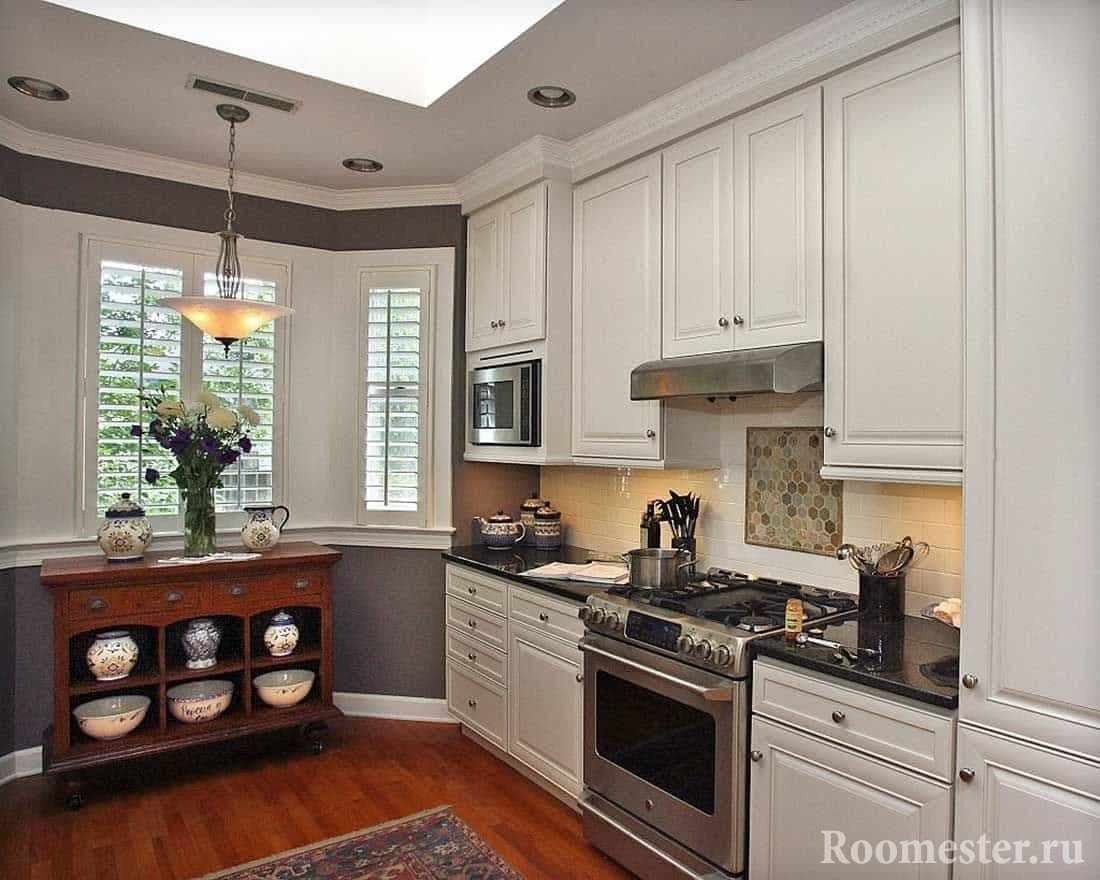Кухня с эркером и деревянным комодом у окна