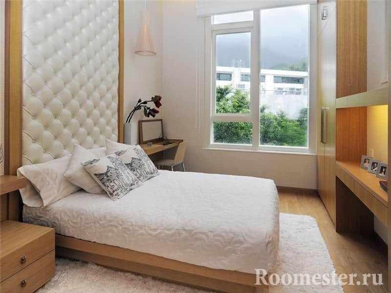 Небольшая кровать с кожаным изголовьем и в спальне с большим окном