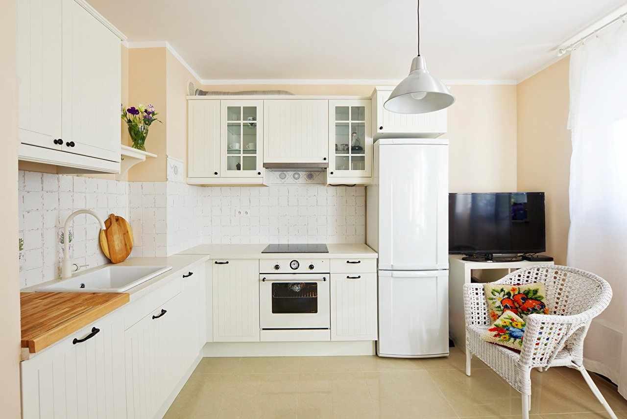 Г-образная планировка кухни с белой мебелью
