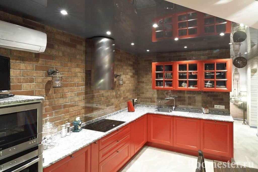 Угловая кухня в красном цвете без верхних шкафов над рабочей поверхностью