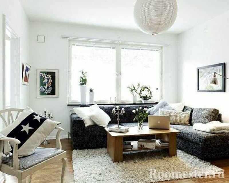 Маленькая гостиная в белом с темным угловым диваном и окном
