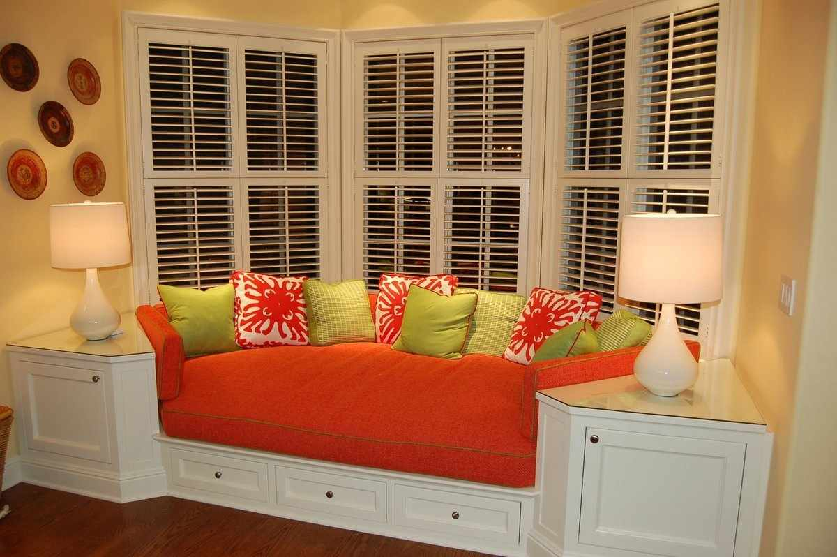 Красный диван с цветными подушками