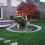 Пруд и дерево с подсветкой перед домом