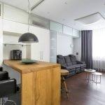 Белая мебель и стол из дерева в квартире-студии