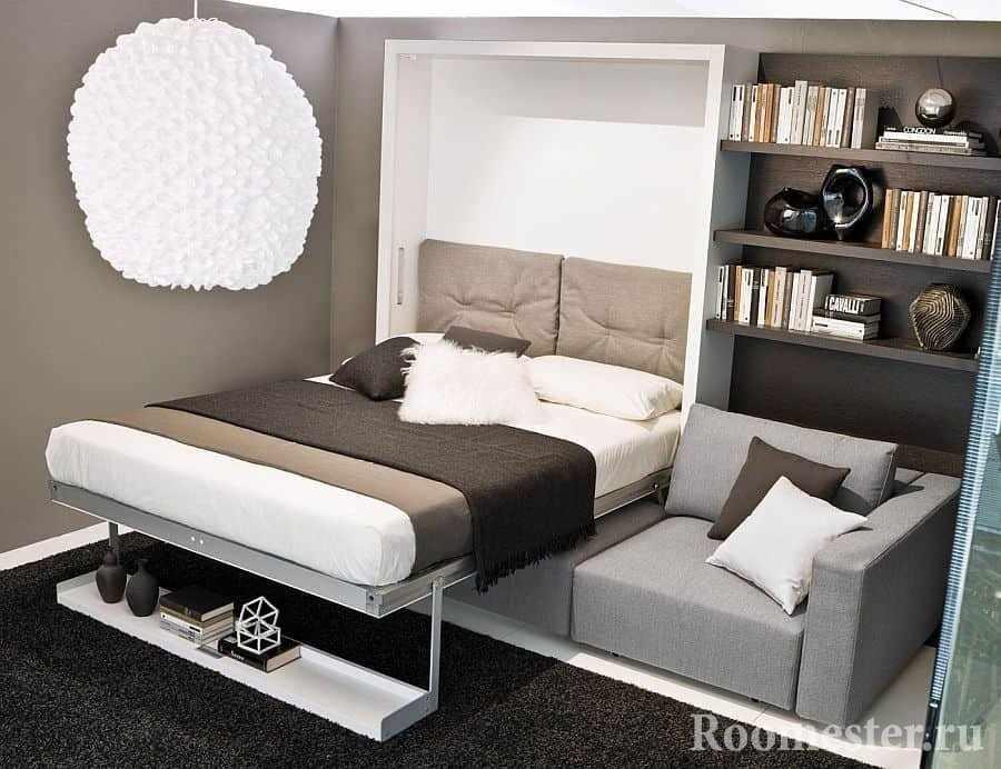 Кровать спрятанная в шкафу над диваном в маленькой комнате