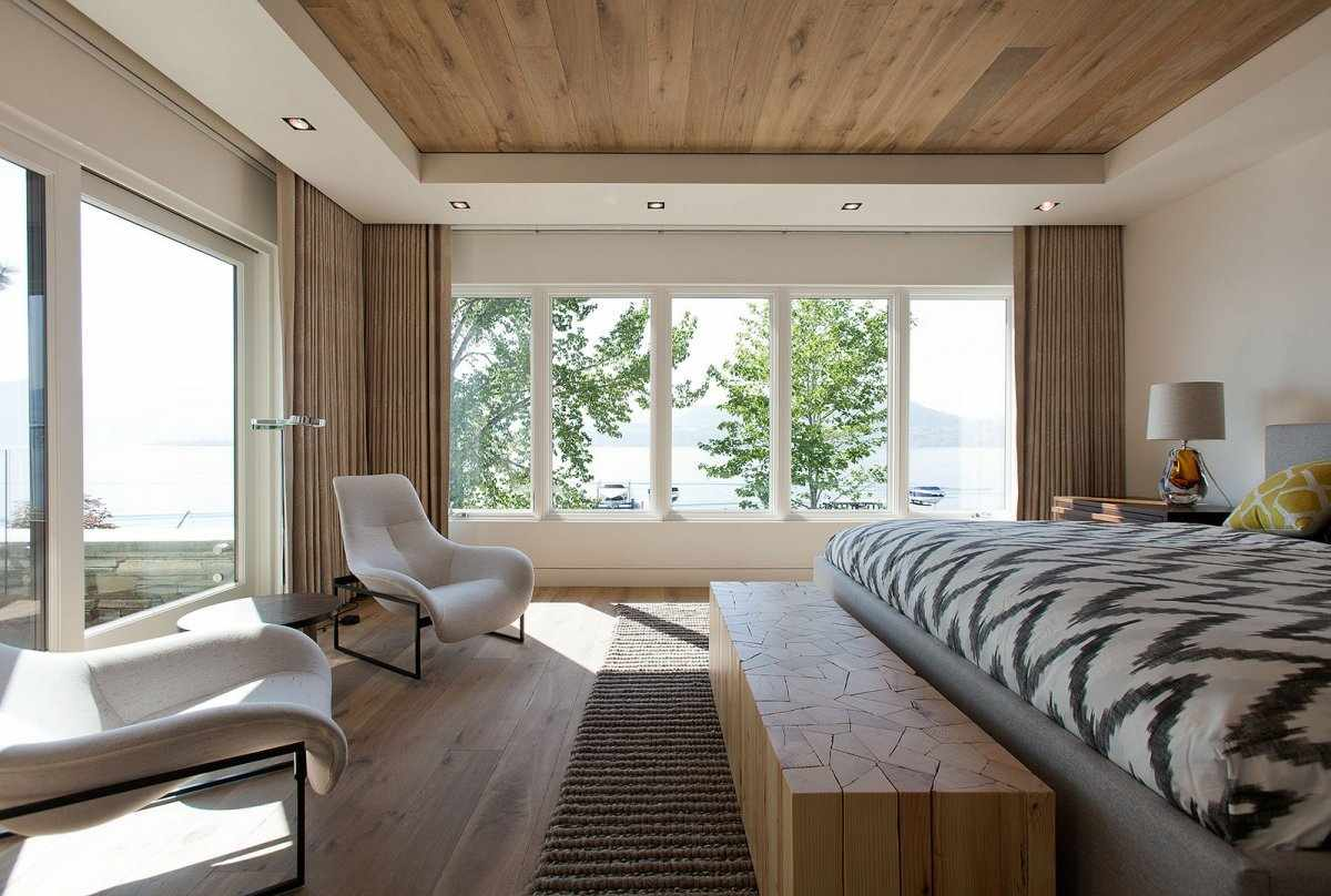Светлая мебель в спальне с двумя окнами