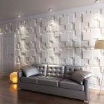 Серый диван на фоне белой стены