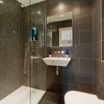 Белая раковина в темном интерьере ванной