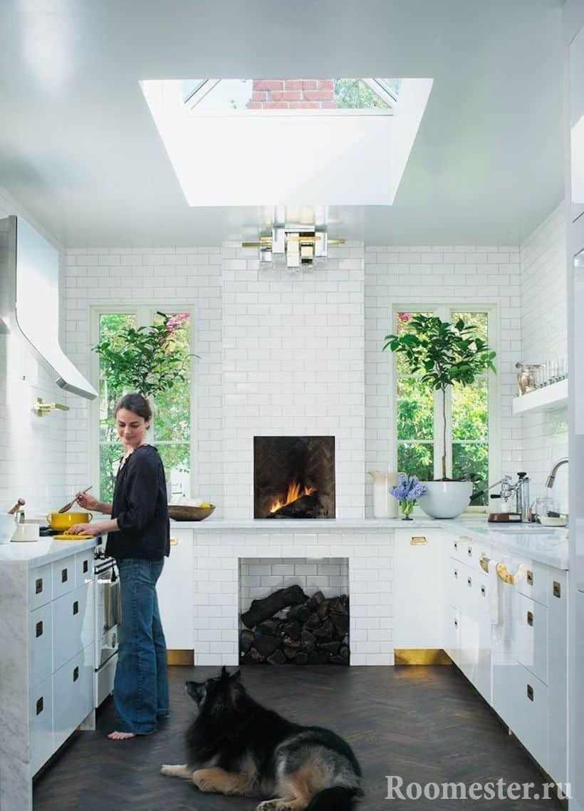 Вытянутая кухня в частном доме с печью и окном в потолке