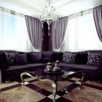 Угловой темно-фиолетовый диван возле окон