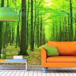 Оранжевый диван на зеленом фоне леса