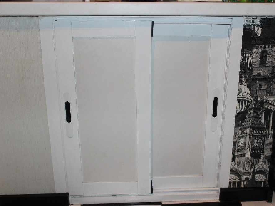 Холодильник с дверками из ЛДСП под окном