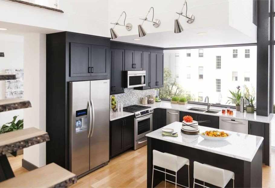 Сочетание стального холодильника и темной мебели на кухне