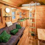 Комната с кухней, диванами и кроватью на втором ярусе