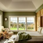 Интерьер спальни с большим окном в зеленых тонах