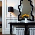 Зеркало в черной раме на белой стене