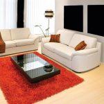 Белые диваны и оранжевый ковер в комнате