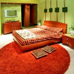 Салатовые стены и оранжевый ковер в спальне