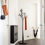 Черная вешалка в форме дерева в белом интерьере