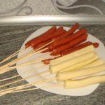Колбаски и сырные палочки насаживаем на шпажки