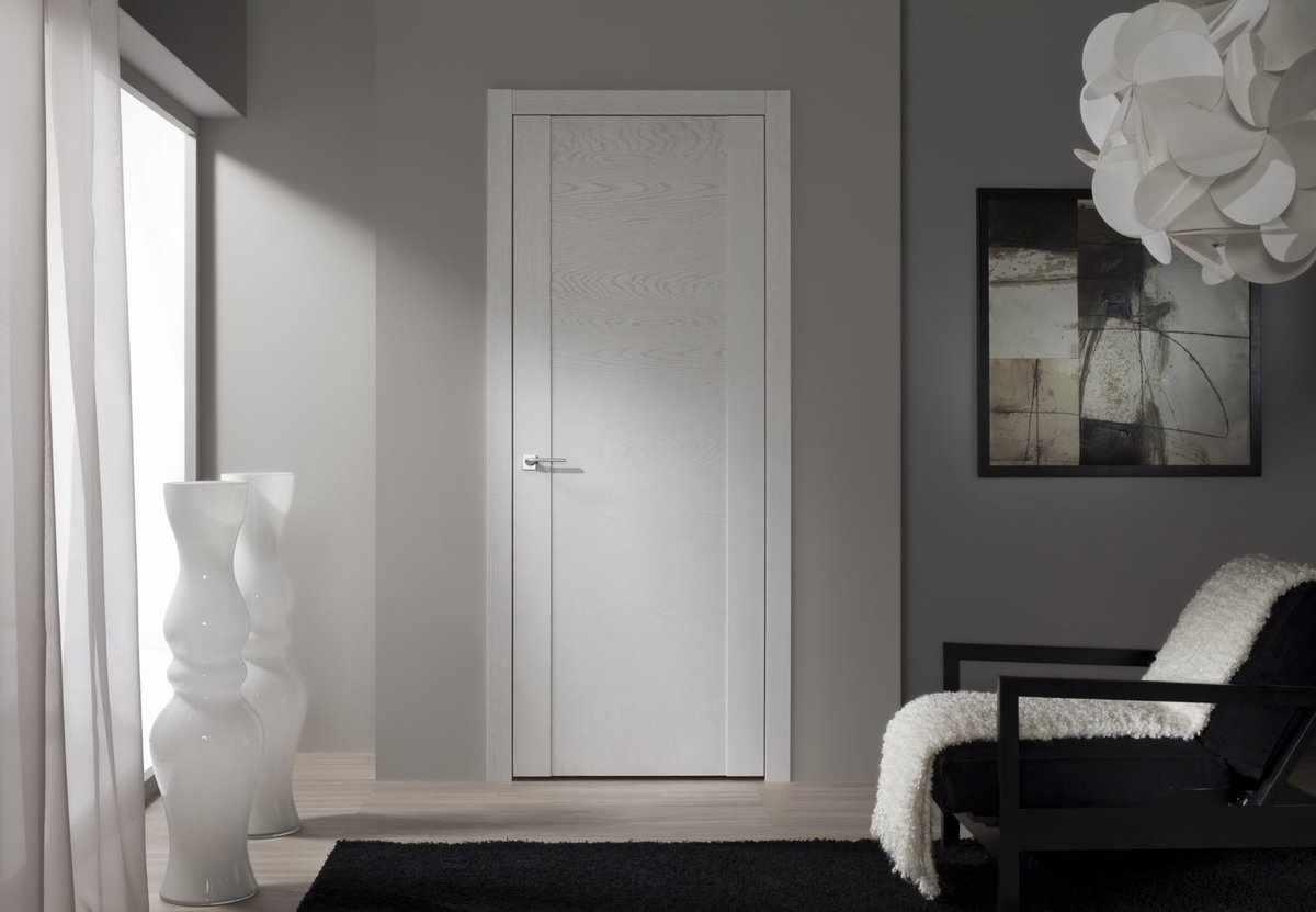 Серые стены и белая дверь в комнате