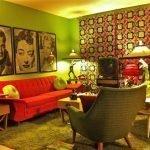 Сочетание салатовых стен и оранжевого дивана