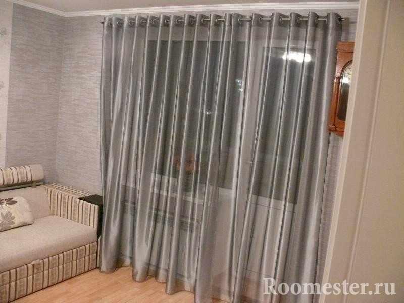 Серые шторы и бежевый диван в комнате
