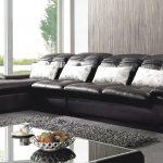 Черный диван со светлыми подушками в комнате