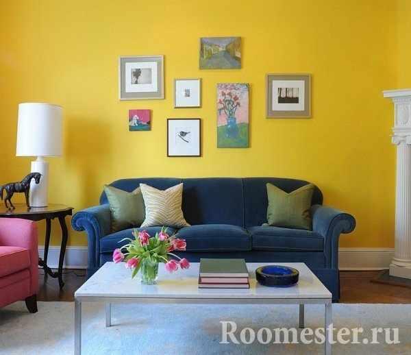 Синий диван на фоне желтой стены